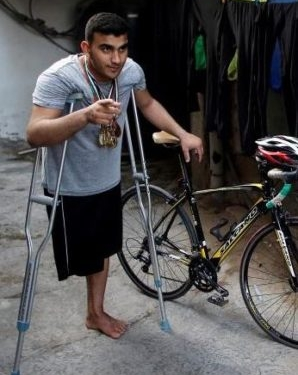 Palestinian cyclist Alaa Al-Daly, 21, who lost his leg by a bullet fired by Israeli troops, stands next to his bicycle at his house in Rafah, southern Gaza Strip, April 18, 2018. A Gaza cyclist's dream of waving the Palestinian flag at the Asian Games has been shattered by an Israeli bullet that caused him to lose his leg after he joined a Gaza border protest. REUTERS/Suhaib Salem