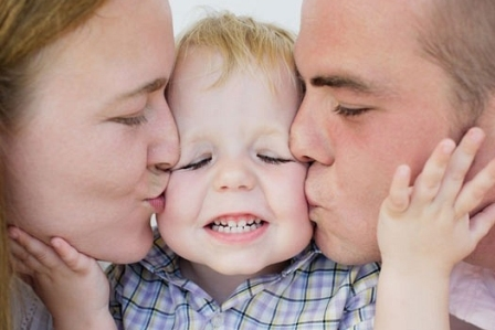Young couple kissing young boy
