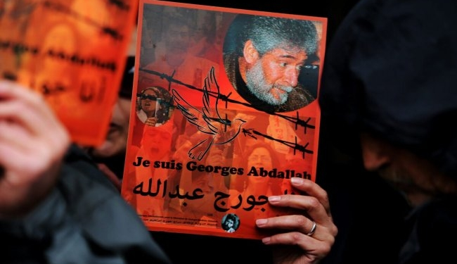 A supporter of Lebanese militant Georges Ibrahim Abdallah holds up a placard bearing his portrait and a slogan in French and Arabic reading: 'I am Georges Abdallah' during a protest outside the French embassy in Beirut demanding his release on February 20, 2015.