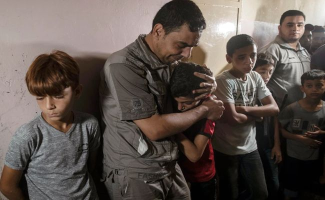 Relatives of Palestinian Omar al-Neil, 12, who was shot by an Israeli sniper during a demonstration on the eastern border between Gaza and Israel, react during his funeral in the family home in Gaza City, Saturday, Aug. 28, 2021